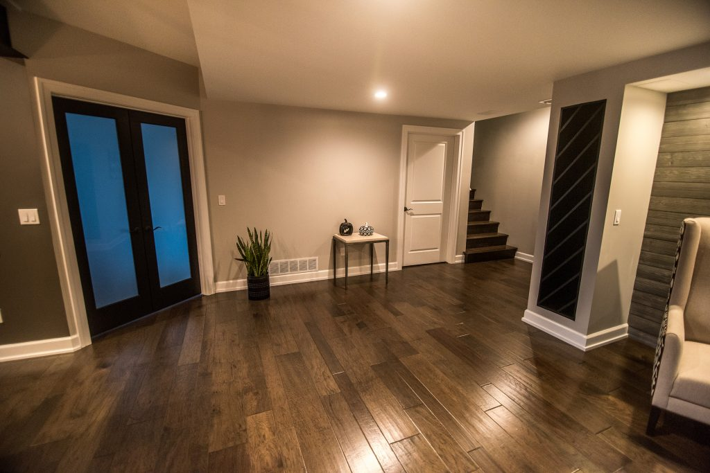 open basement living space leading to spare bedroom with french doors