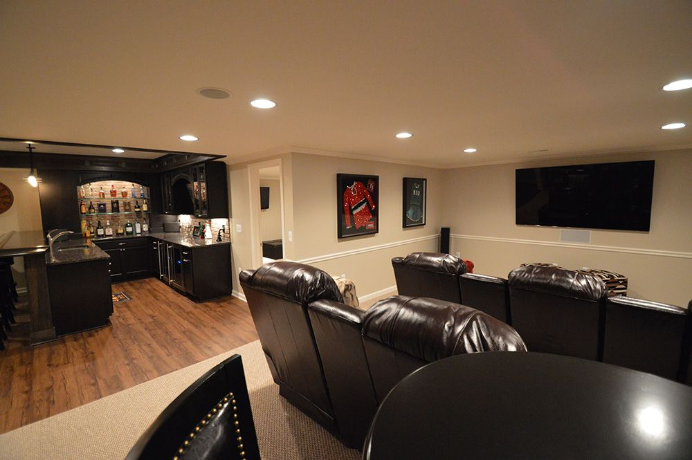 basement with theater and bar area carpeting and vinyl plank flooring