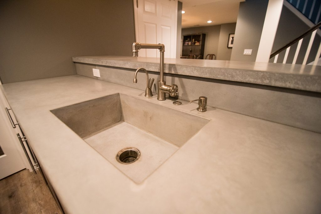 concrete countertops with built in sink and rustic faucets