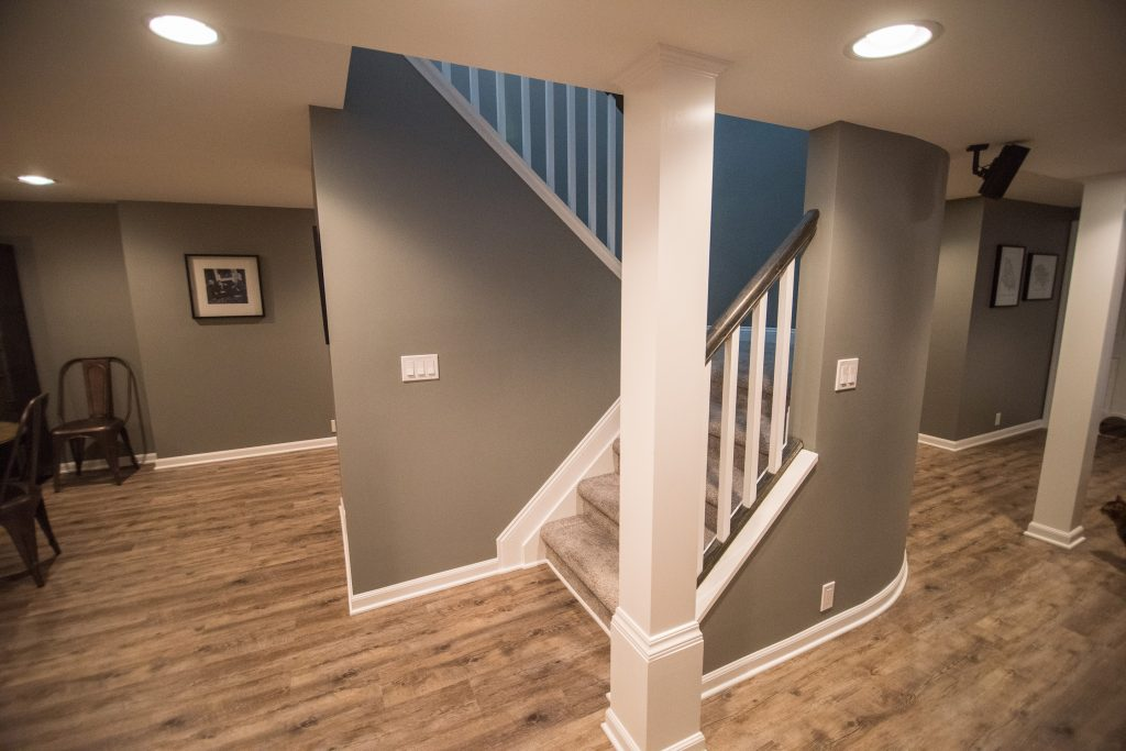 rounded staircase wall in basement with carpeting