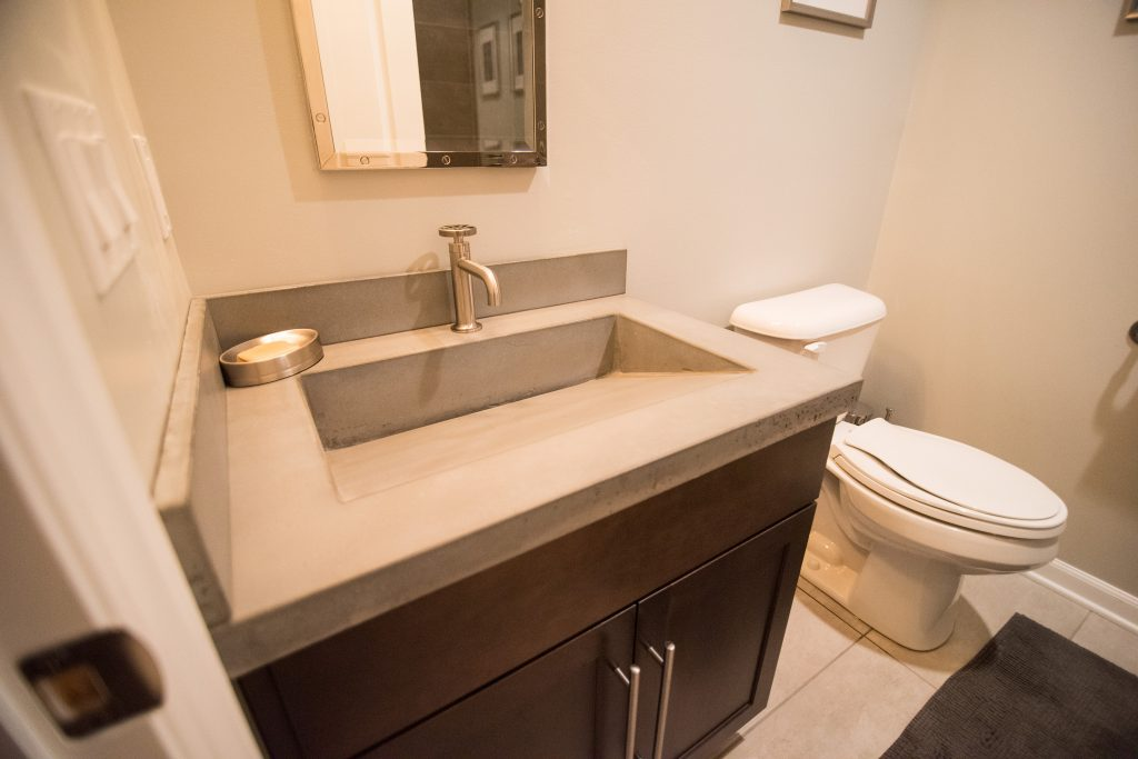 basement bathroom with vinyl tile flooring and concrete countertops