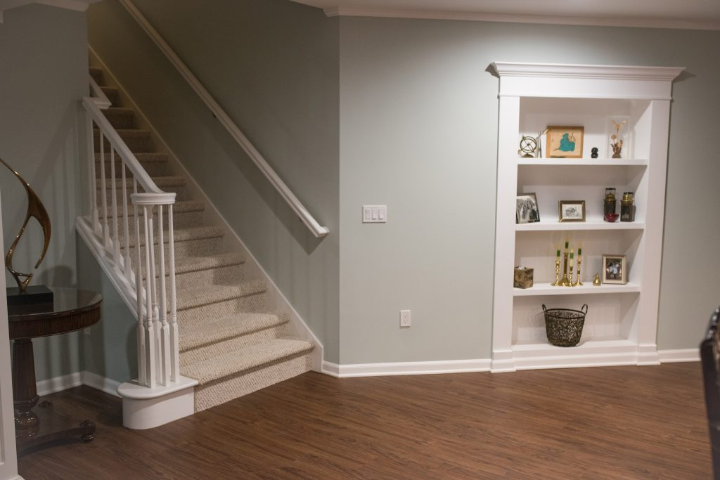 basement staircase with secret bookcase door and vinyl plank flooring