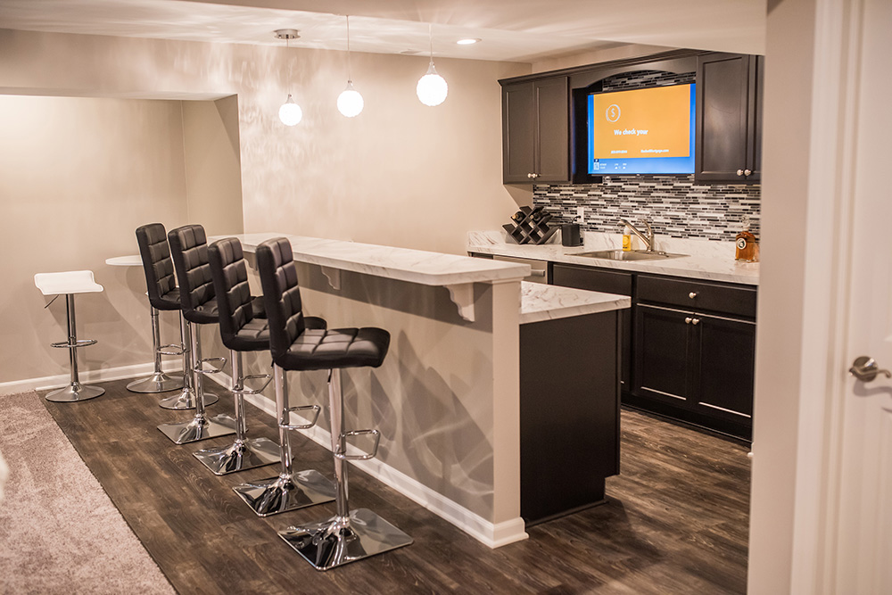 basement bar with dark cabinets and white countertop