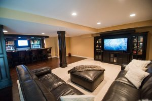 open concept living and dining in basement with large bar and media center