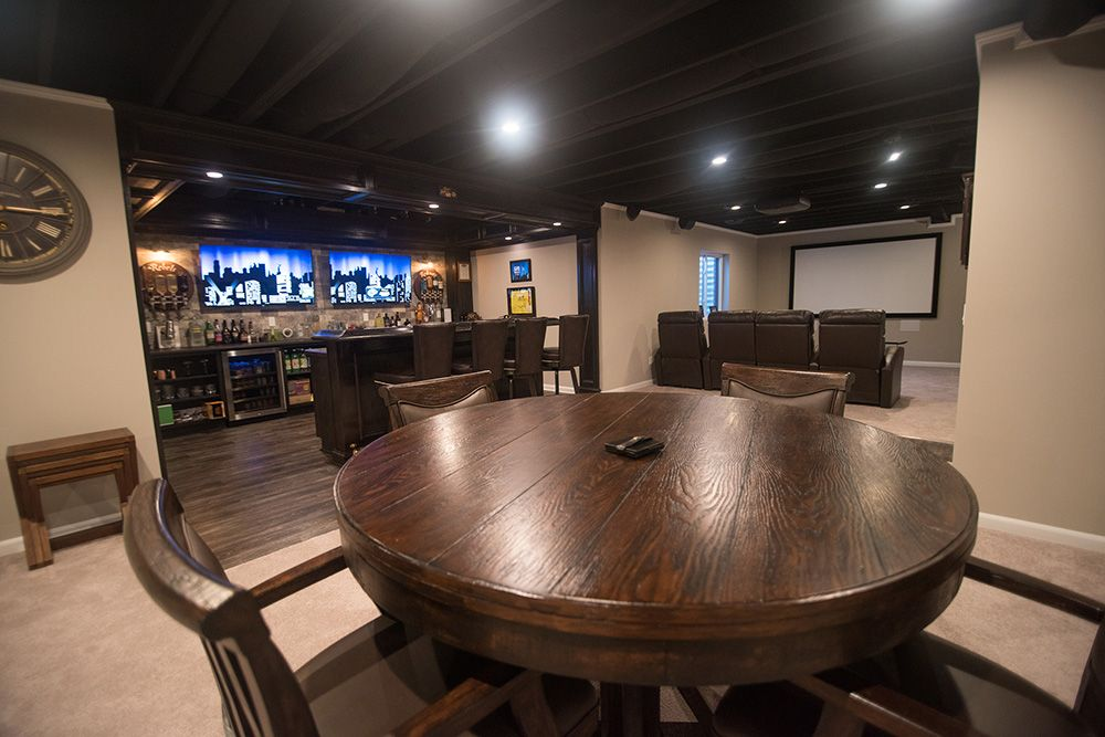 spacious basement with home bar and theater space painted ceiling and carpet