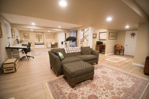 basement living room with vinyl plank flooring and sectional couch