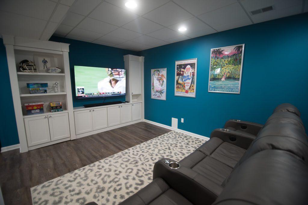 bright blue finished basement living room with custom book shelf