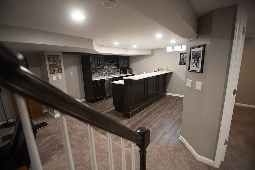 vinyl plank flooring with basement kitchen with dark cabinets and white countertops