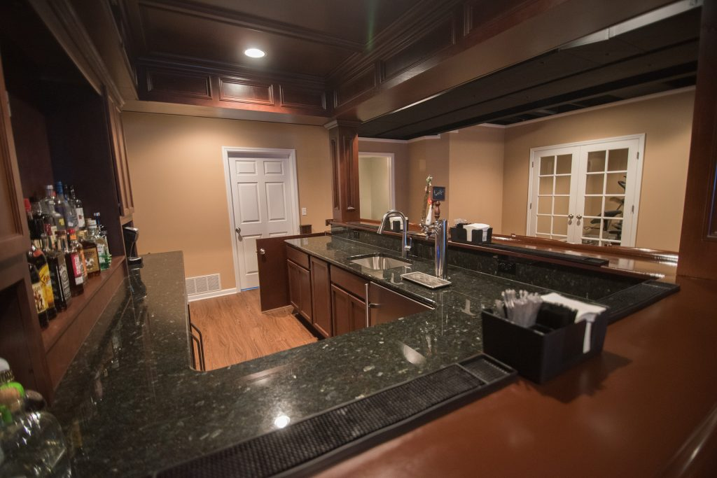 basement bar with granite countertops and vinyl plank flooring