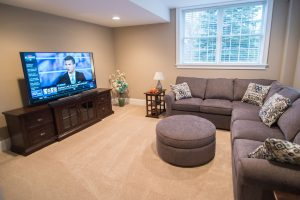 carpeted basement flooring with a couch and tv