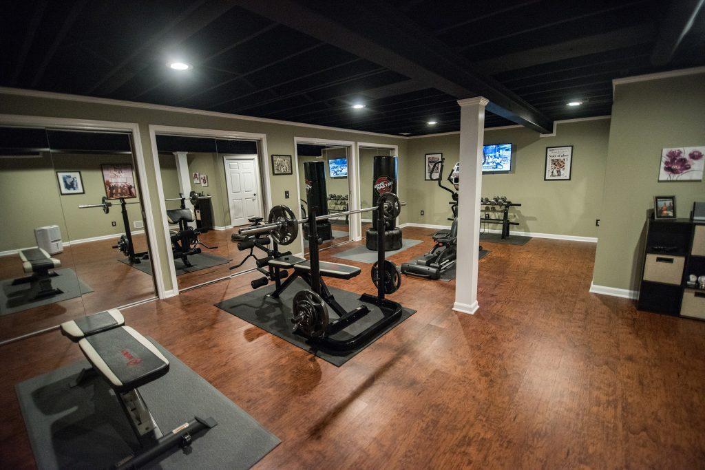 basement fitness room with vinyl plank flooring