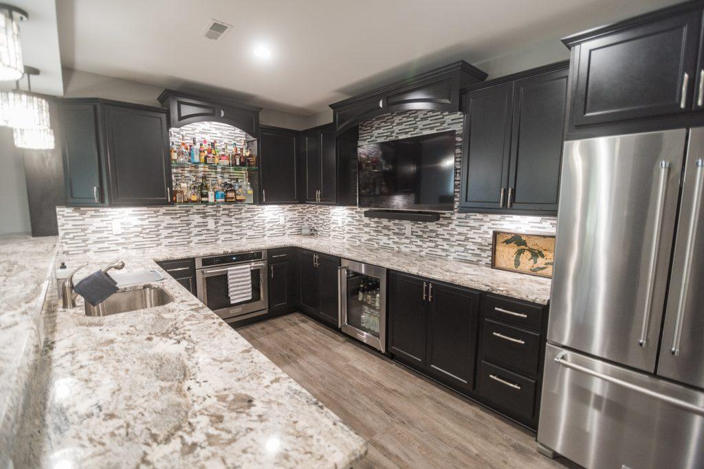 basement kitchen with vinyl plank flooring and dark cabinets