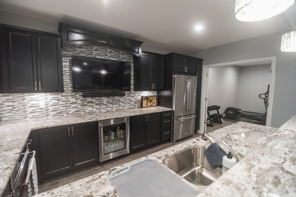finished basement with custom kitchen with glass backsplash