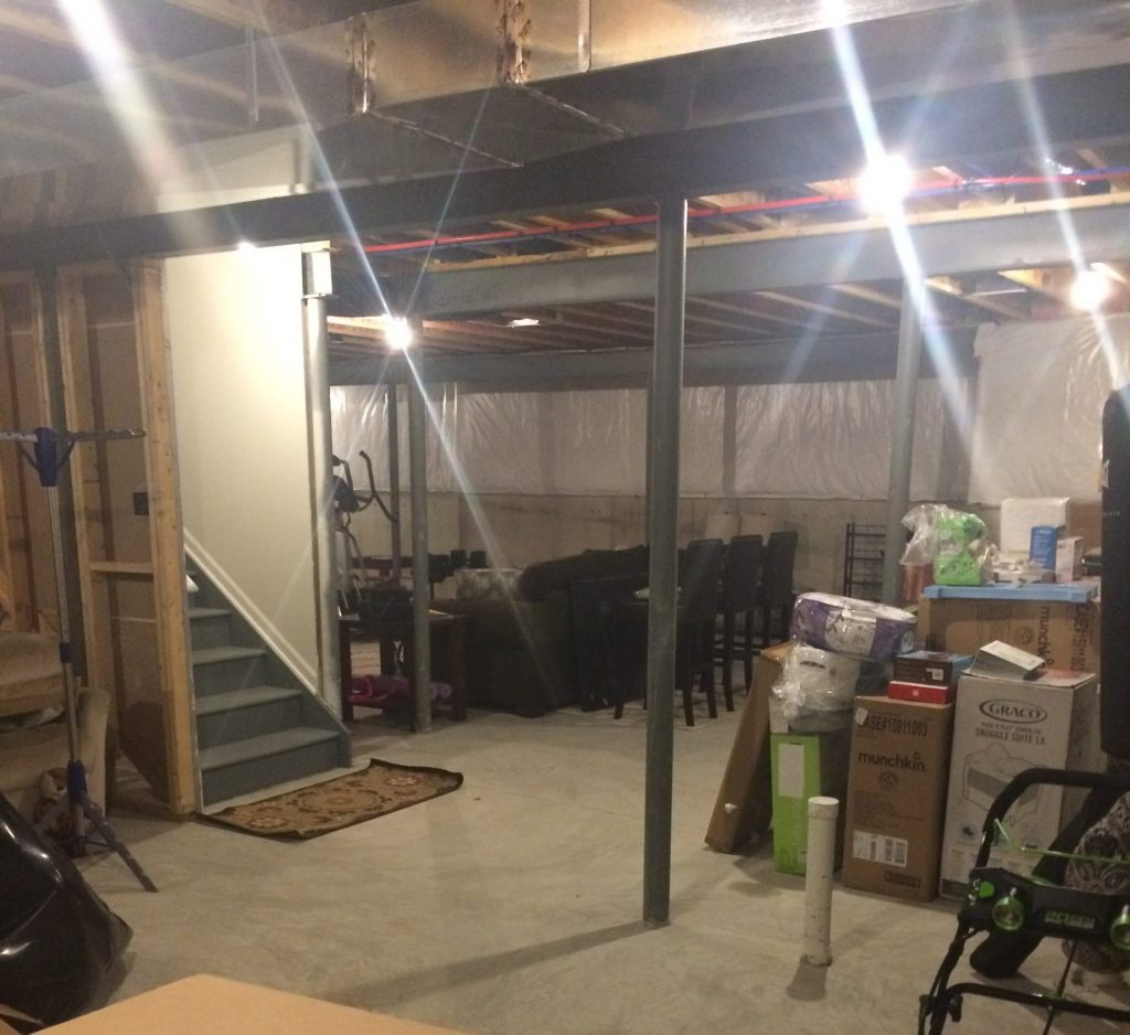 unfinished basement in south lyon michigan with poles and staircase