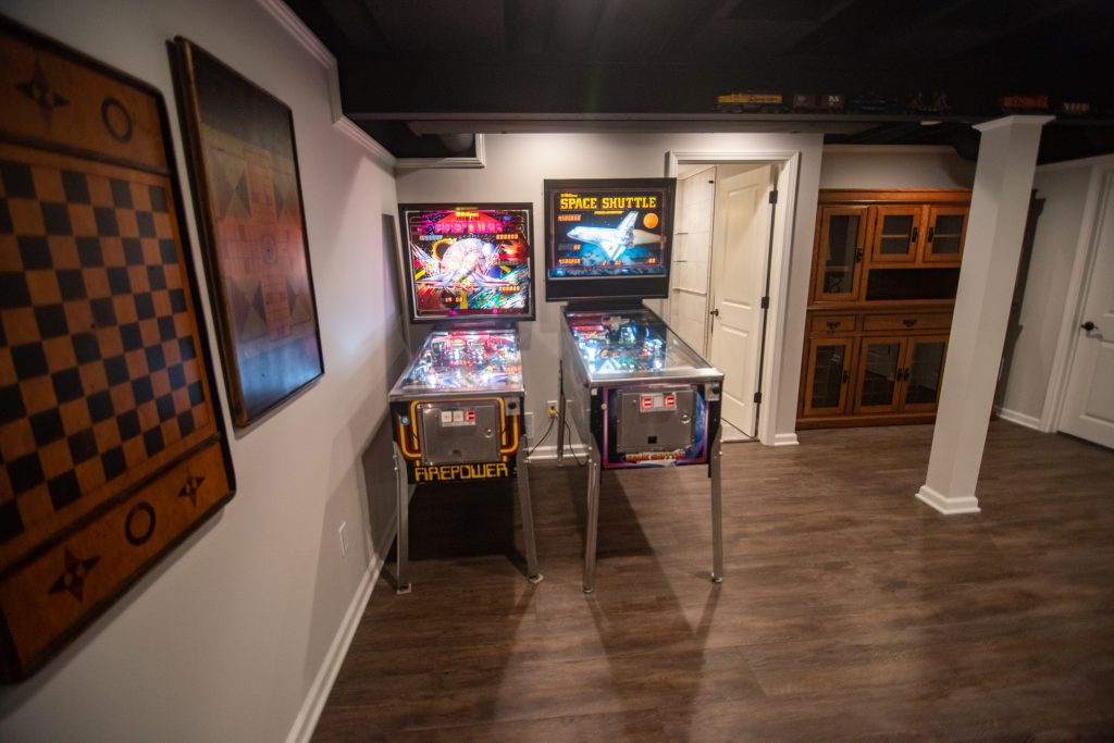 pinball machines in basement with hickory vinyl plank flooring