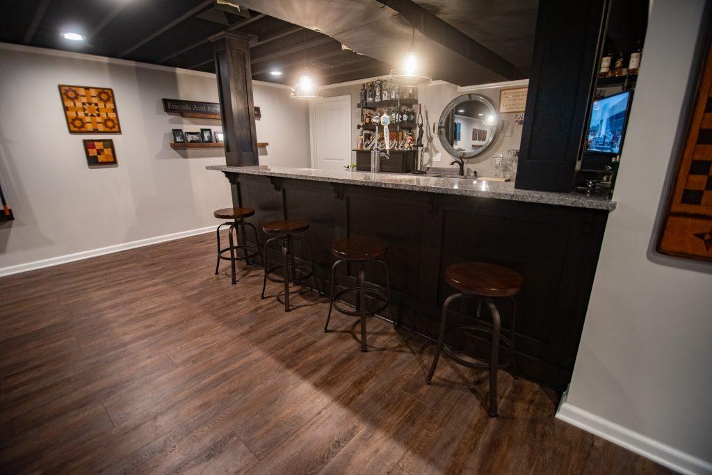 basement bar with dark cabinets and granite countertops