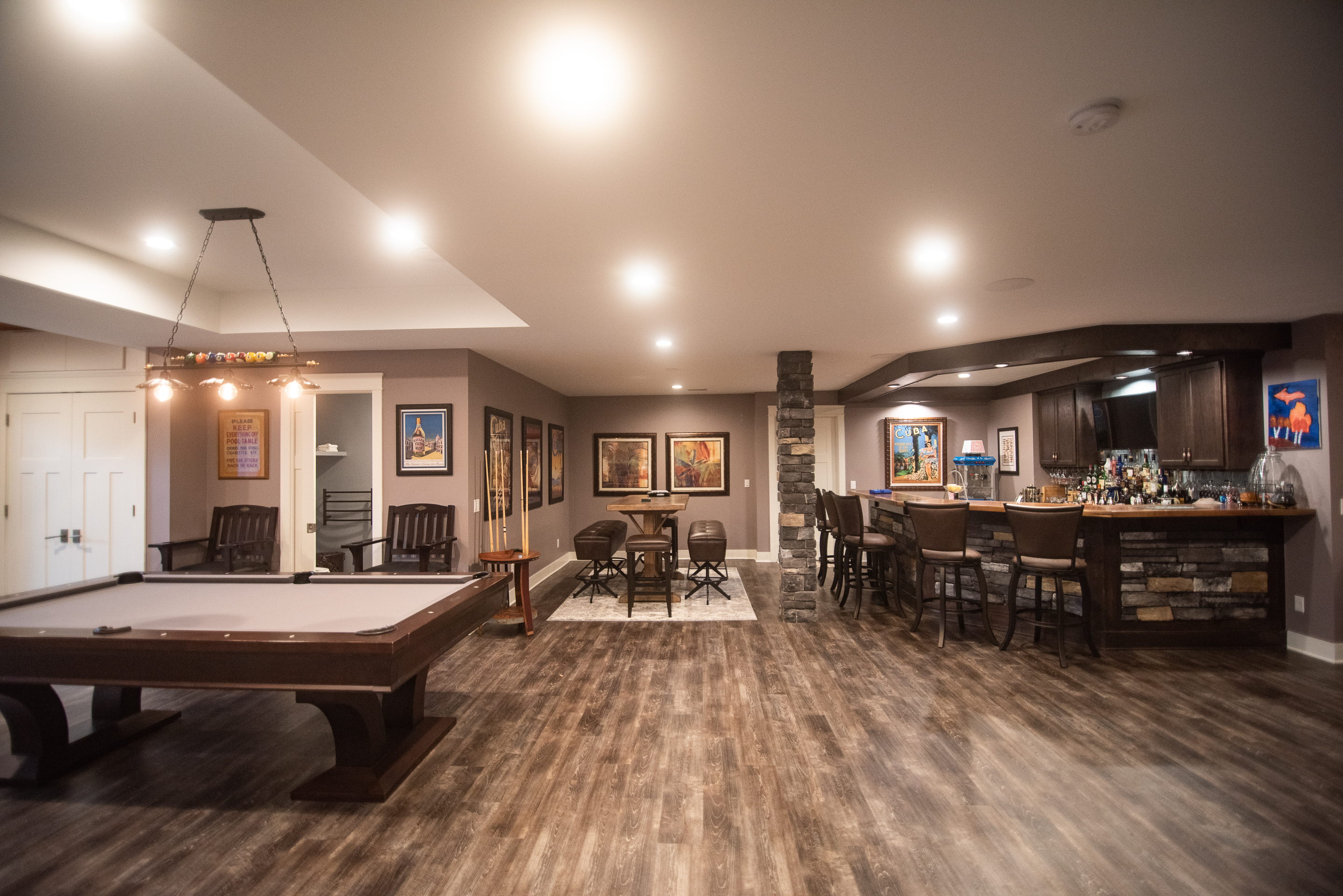 finished basement with open space vinyl plank flooring and brown tones