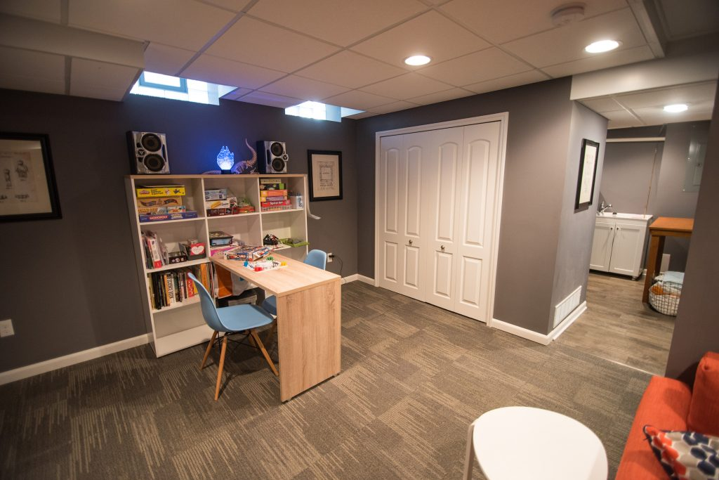 kids area in basement with shelving and table for games